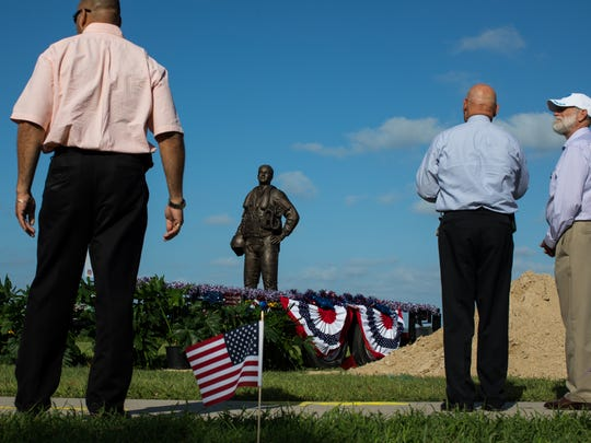 People gather around the Naval Aviator Memorial statue on display before its ground breaking at Ropes Park on Thursday, June 15, 2017.