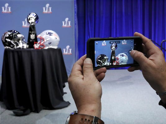 An attendee snaps a photo of the Vince Lombardi Trophy and team helmets during NFL Commissioner Roger Goodell's press conference at Super Bowl 51, Wednesday, Feb. 1, 2017, in Houston. The Atlanta Falcons will face the New England Patriots in the Super Bowl Sunday. (Curtis Compton/Atlanta Journal-Constitution via AP)