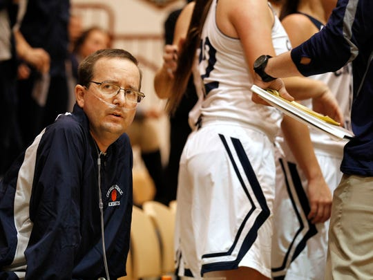 Central Catholic assistant girls basketball coach Jeff Dienhart looks to the scoreboard during a break in the action of the J&C Hoops Classic. Dienhart is hooked to an oxygen tank as he suffers from cystic fibrosis, a genetic disorder that affects the lungs. He is about to travel to the Dominican Republic for a controversial stem cell procedure that is not approved by the United States Food and Drug Administration.