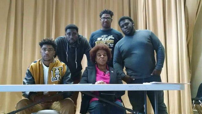 Defensive back Jarnell Harris (sitting, far left) signed to play at Independence Community College in Kansas.