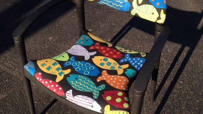 Outlines dictate the space for colorful fish painted onto fabric.