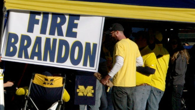 Michigan fans show their displeasure with the athletic director during a tailgate before Saturday's game in Ann Arbor.