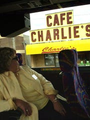 Yvonne Kramer looks at the Charlie's Cafe sign in Freeport during a 2002 tour of the Central Minnesota area that inspired Lake Wobegon.