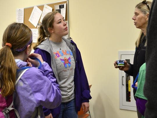 Committee on Temporary Shelter Peer Support Staff member Ciara Kilburn answers questions about the Daystation while speaking to Melissa Wolaver, right, and Anna Hauf, 10, left, during the annual COTS Walk in Burlington on Sunday, May 7, 2017.