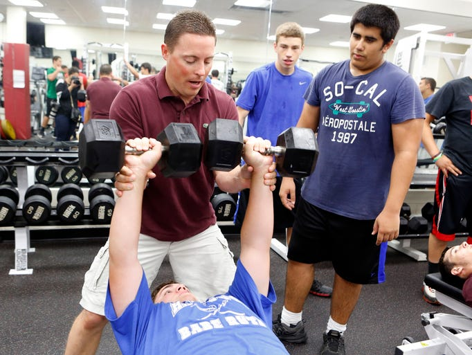 Harrison football coach Dom Zanot will take over for a Harrison icon, Art Troilo Jr., who coached the team for 28 seasons. Coach Dom Zanot demonstrates the proper way to spot during practice in the weight room, July 18, 2014 at Harrison High School. Strength and conditioning will be a big part of his imprint on the program.