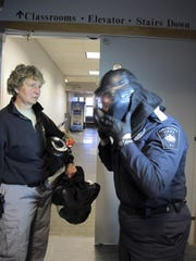 Colchester Police Chief Jennifer Morrison (right) dons a protective helmet during an active shooter training session at the University of Vermont in Burlington. At left is UVM Police Chief Lianne Tuomey, one of the instructors.