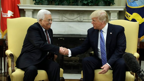 President Donald Trump shakes hands with with Palestinian