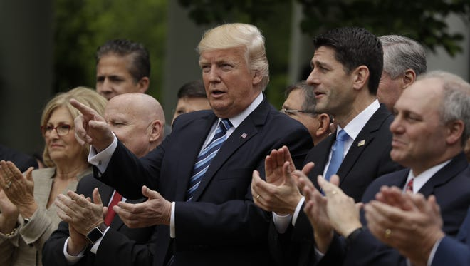 President Donald Trump, House Speaker Paul Ryan of Wis., and others, applaud in the Rose Garden of the White House in Washington, Thursday, after the House pushed through a health care bill.