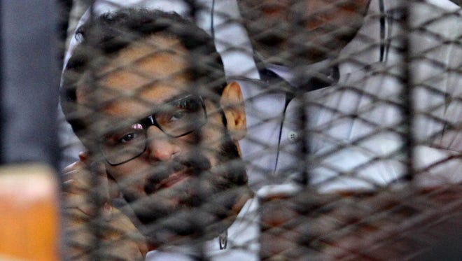 American-Egyptian activist, Mohamed Soltan sits behind bars in an Egyptian courtroom during his trial June 23, 2014, in Cairo.