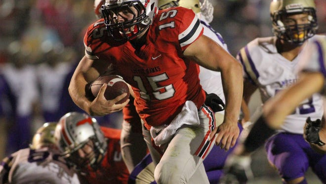 City High quarterback Nate Wieland bursts through a hole in the Muscatine defense to score the Little Hawks' first touchdown late in the first quarter at Frank Bates Field Friday, October 7, 2016.
