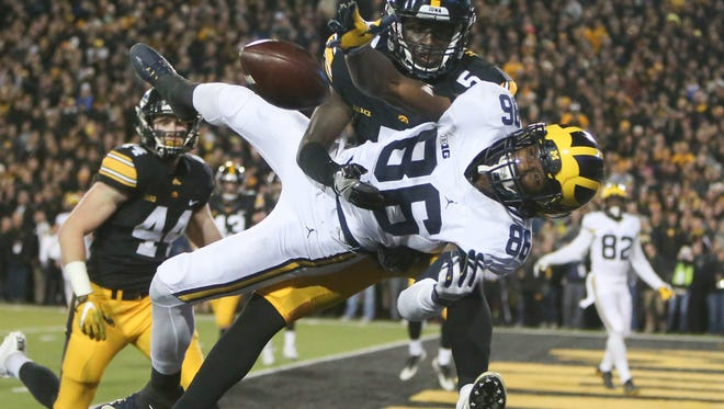 Michigan's Jehu Chesson is defended by Iowa's Manny Rugamba during the first half Saturday in Iowa City, Iowa.