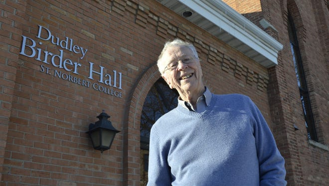 Dudley Birder, who has worked at St. Norbert College as a music teacher and director since 1958, stands outside Dudley Birder Hall at the corner of Grant and Fourth streets in De Pere.