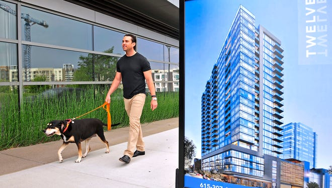 Twelve Twelve condo resident Parker Turner walks his dog Bella outside the residential building. The telecom executive picked Nashville to live because it was one city he never wanted to leave when he came here on business trips.