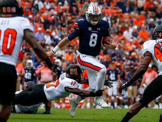 Auburn quarterback Jarrett Stidham (8) tries to elude the tackle of Mercer defensive back Eric Jackson (17) as he scrambles for yardage during the first half of an NCAA college football game, Saturday, Sept. 16, 2017, in Auburn, Ala.
