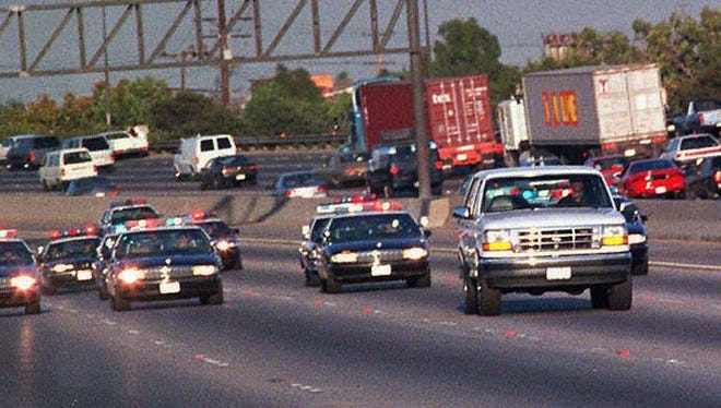 On June 17, 1994, Law enforcement vehicles keep a close tail on a white Ford Bronco carrying O.J. Simpson during a northbound chase on the 405 San Diego freeway in Los Angeles county.  Simpson was driven by Al Cowlings, a lifelong friend and teammate to his California home.