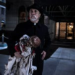 "Tony Amendola as Father Perez with the Annabelle doll in ""Annabelle,"" which hits theaters this weekend."