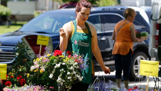 Mackenzie Mraz, retail manager for Hartman's Town and Country Greenhouse, moves flowers during the Garden Fair at Washington Park Saturday, Jun. 10, 2017, in Manitowoc, Wis. Josh Clark/USA TODAY NETWORK-Wisconsin