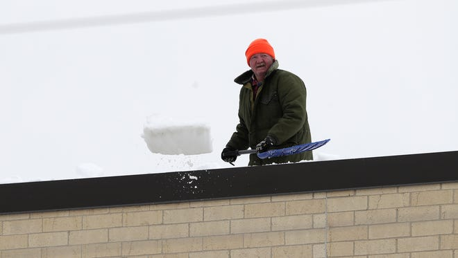 A man shovels snow from the roof of the gym at De Pere High School. The district temporarily closed the gyms at the high school and at Foxview Intermediate School on Wednesday after they noticed the roofs were sagging under the weight of about 2 feet of snow that fell over the weekend.