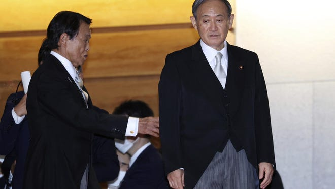 Newly elected Japanese Prime Minister Yoshihide Suga, right, waits his cabinet members for a photo session after their first cabinet meeting at the prime minister's official residence in Tokyo Wednesday, Sept. 16, 2020. Japan's Parliament elected Yoshihide Suga as prime minister Wednesday, replacing long-serving leader Shinzo Abe with his right-hand man.