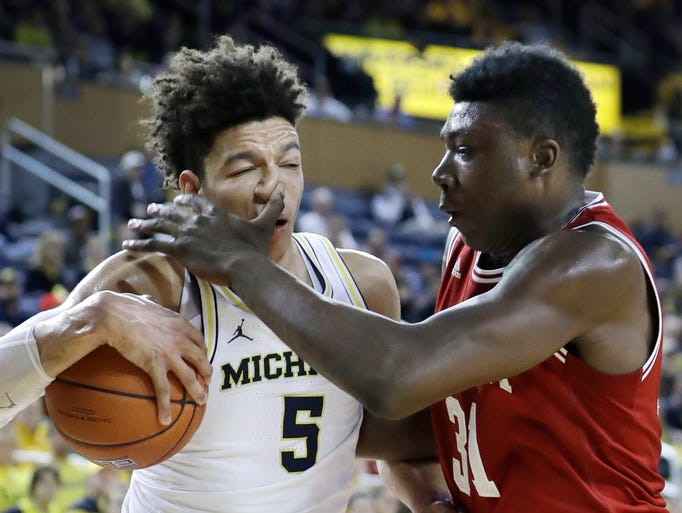 Michigan forward D.J. Wilson (5) is fouled by Indiana