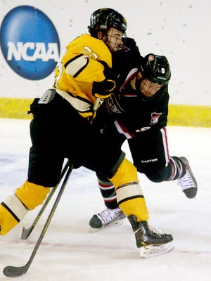 Michigan Tech forward Mike Neville, left, and St. Cloud State forward Joey Benik, battle for the puck during the first period of a regional semifinal in the NCAA college hockey tournament, Friday, March 27, 2015, in Fargo, N.D.