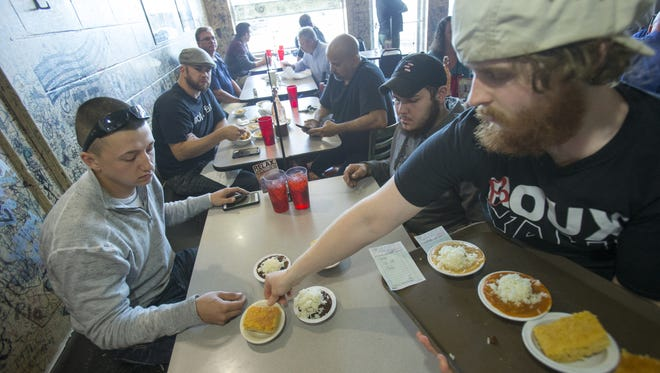 Justin Stauffer (left), and friend Hunter Bowman get side dishes from waiter Andrew Cutshaw, at Papa Roux, the Eastside Cajun restaurant that is offering a 25 percent discount to people with a handgun license, Monday, Oct. 26, 2015. Both men used their permits to get discounts, and said they carried firearms to lunch.