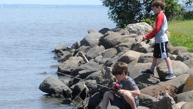 Two young boys fish on the shores of Lake Winnebago at Lakeside Park in June of 2015.