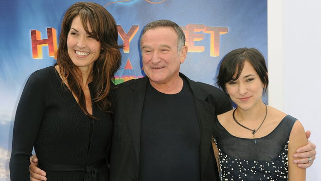 "Susan Schneider, from left, Robin Williams, and Zelda Williams arrive at the premiere of  ""Happy Feet Two"" at Grauman's Chinese Theater, in Los Angeles on Nov. 13, 2011. Attorneys for Robin Williams' wife and children are headed to court in their battle over the late comedian's estate."