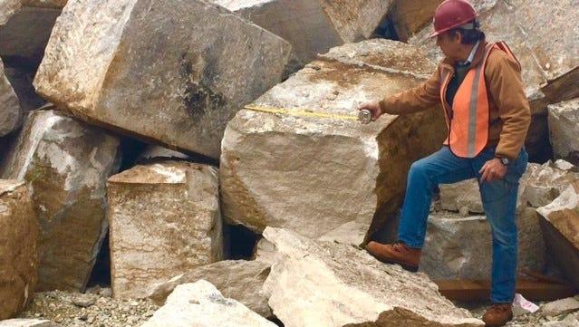 Sculptor Fletcher Golden stands amid the limestone blocks at the Frisco Bridge.