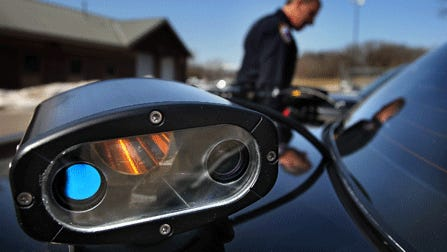 A police officer prepares to go out on patrol using a license plate reader, which photographs license plates and then compares them with those in a database of stolen vehicles. Some states are considering limits on how long police can keep the data.