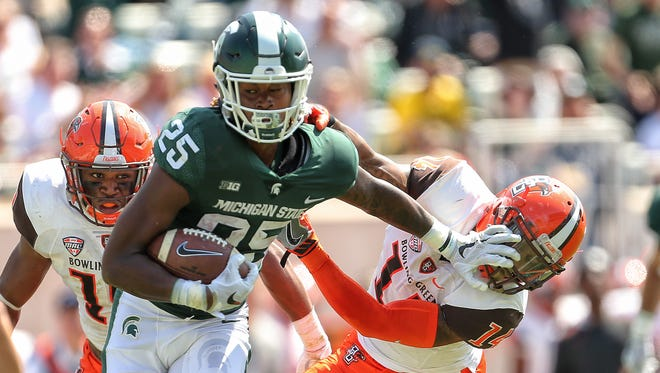 Michigan State wide receiver Darrell Stewart Jr. (25) stiff arms Bowling Green defensive back Marcus Milton (14) during the first half of a game at Spartan Stadium.
