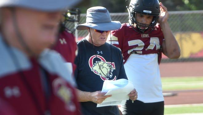 After the stunning resignation of head coach Jim Benkert, center, the Oaks Christian football program has plenty of questions moving forward.