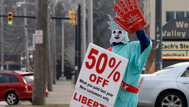 Brittney Freison, dressed as Lady Liberty, waves to motorists near the Liberty Tax Service office in Berea, Ohio.