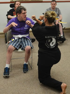 Fred W. Schwoerer does a blocking exercise to receive his gold belt with instructor Shelly Deterville.