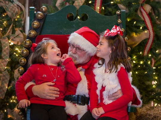 Dressa Alexander, 5, and Presley Royalty, 6, sit on Santa's lap to tell him what they would like for Christmas as they spend the day at Blue Moon Stables in Corydon, Ky., for Christmas on the Farm on Saturday afternoon.