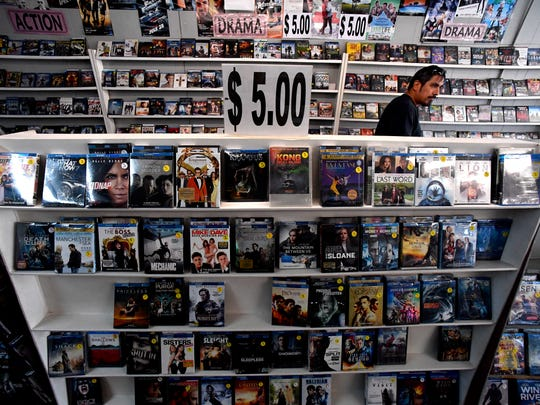 David Gonzales of Haskell searches the shelves for discounted movies at Video Mania in Anson.