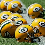 Helmets sit on the practice field during a Green Bay Packers organized team activities day.