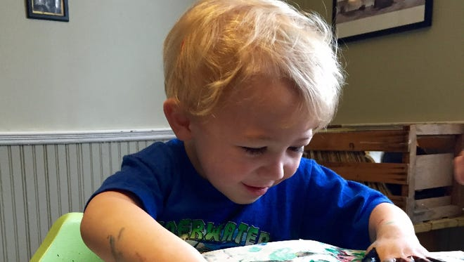 Two-year-old Cash Nance enjoys finger painting at his family's table. Cash was diagnosed with autism. Sensory activities are important part of his treatment.