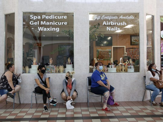 Customers wait for to get their nails done 4at the Nail Tech salon in the Yuba Sutter Mall in Yuba City, Calif., Wednesday, May 6, 2020. Several dozen shoppers streamed into the first California mall to reopen Wednesday, despite California Gov. Gavin Newsom's orders restraining businesses because of the coronavirus pandemic. (AP Photo/Rich Pedroncelli)