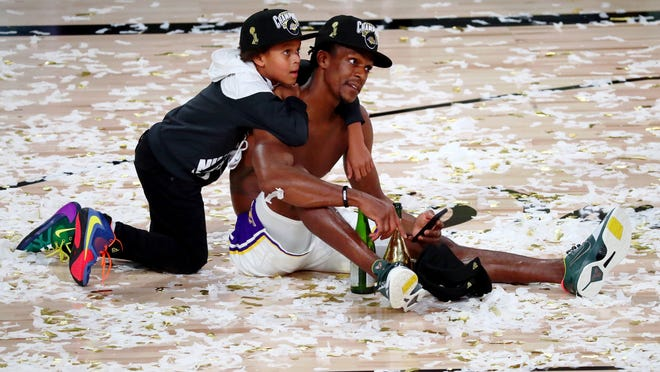 Los Angeles Lakers guard Rajon Rondo (9) sits on the court with his son after game six of the 2020 NBA Finals at AdventHealth Arena on Oct. 11, 2020. The Los Angeles Lakers won 106-93 to win the series.