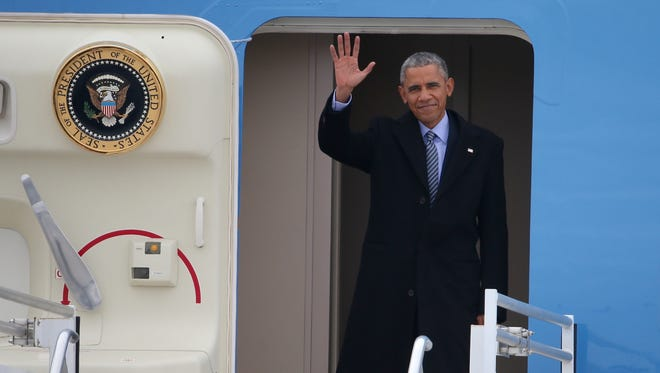 President Barack Obama waves as he exits Air Force One after landing at Indianapolis International Airport.