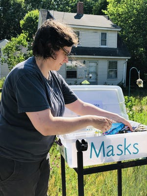 Cricket Wise places the new face masks that she made into the bin from which she sells them on Cat Mousam Road in Kennebunk.