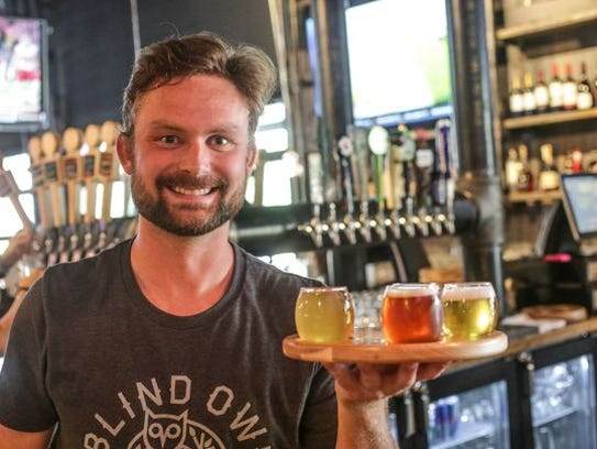Drew Lee holds a beer flight at the Blind Owl Brewery,