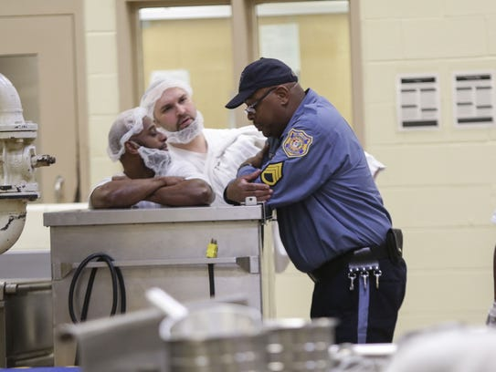 (left to right)Inmates Dashawn Brooks and Neil Carrier talk with correctional officer Steve Burton while working in the kitchen at James T. Vaughn Correctional Center.