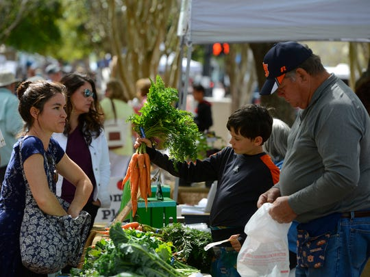 Mathew Cichon of Stewart Farms helps customers Saturday at the Palafox Market in downtown Pensacola.
