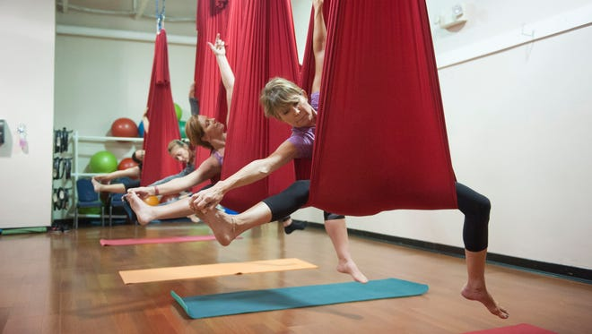 Debbie Tamburri of Cinnaminson (from right), Gloria Wolfgang of Cherry Hill, and Kate Christopher of Marlton, participate in an aerial yoga class at Future Fitness Powered by AFC in Cherry Hill.