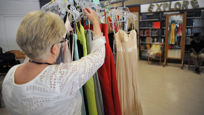 Millville Senior High School sewing teacher Penny Davish places a prom dress back on a rack in the library, Tuesday, Mar. 22, 2016.