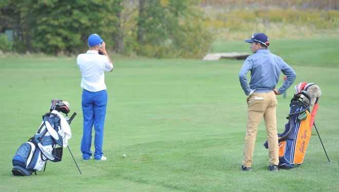 Ontario's Lane Thomas uses his rangefinder on the 15th hole at Red Hawk next to Galion's Spencer Keller.