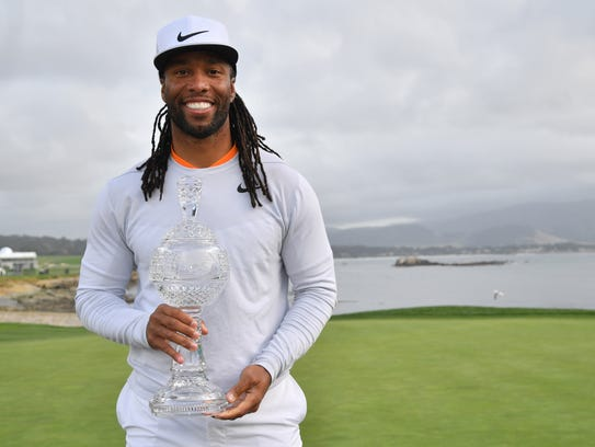 Larry Fitzgerald poses with the amateur trophy after winning the AT&T Pebble Beach Pro-Am on Sunday.