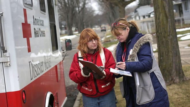 Red Cross volunteers Linda Giddings of Millington, MI, left and Sandra Garza of South Bend, IN coordinate distribution of water, water filters and testing kits in Flint on Tuesday, January 26, 2016.